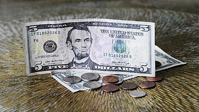 Ein Dollarschein und mehrere Münzen aus den USA.