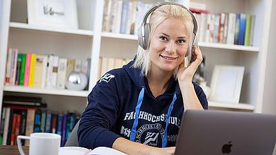 Eine Studierende sitzt mit Kopfhörern vor ihrem Laptop.