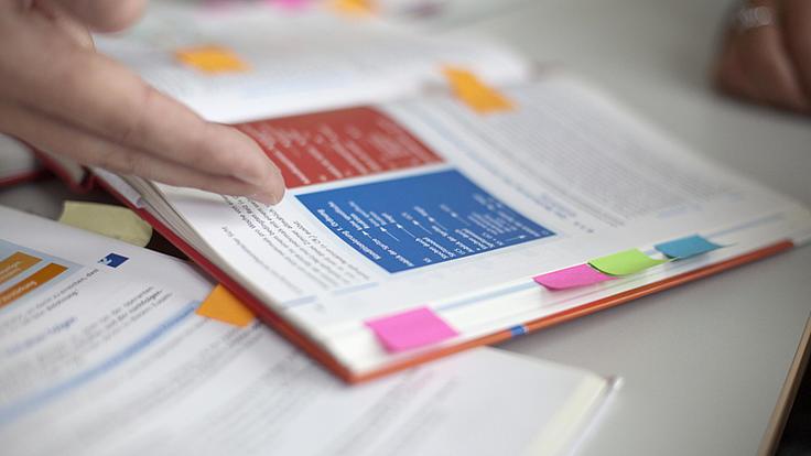 Eine Hand zeigt auf ein geöffnetes Buch mit bunten Grafiken und Post-it-Markierungen an verschiedenen Seiten.