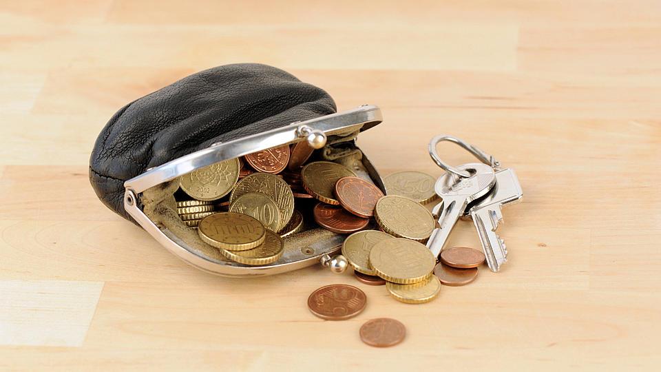 Ein Geldbeutel mit Münzen und einem Schlüssel.