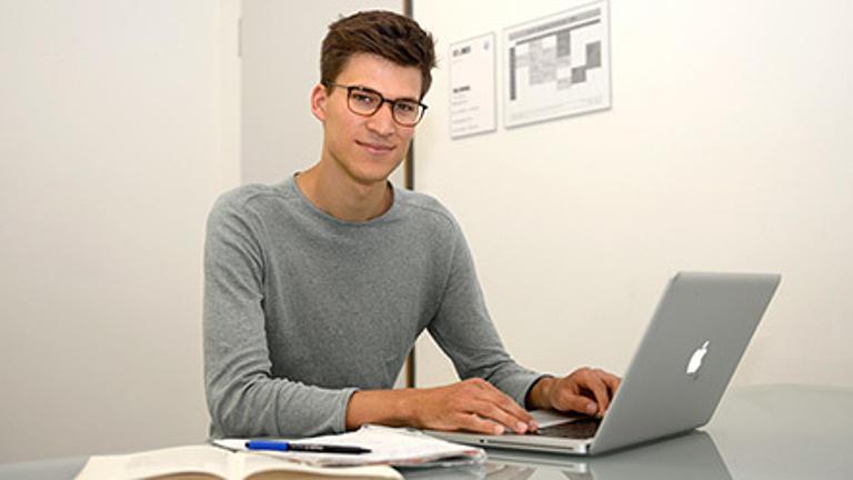 Ein junger Mann sitzt an einem Laptop.