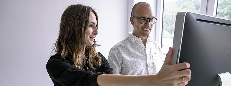 Eine Frau und eine Mann mit Brille schauen auf einen Computerbildschirm