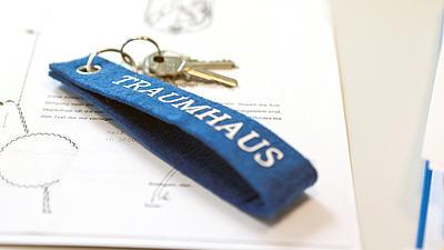 Auf einem notariellen Schriftstück liegt ein Schlüssel mit einem blauen Schlüsselanhänger aus Filz mit der Aufschrift Traumhaus.