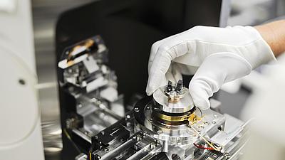 Eine Hand im Gummihandschuh hält ein Kunststoffbauteil in eine Vorrichtung.