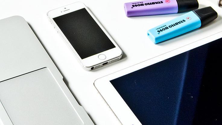 Tablet, Handy, Textmarker und Laptop liegen auf einem Tisch.