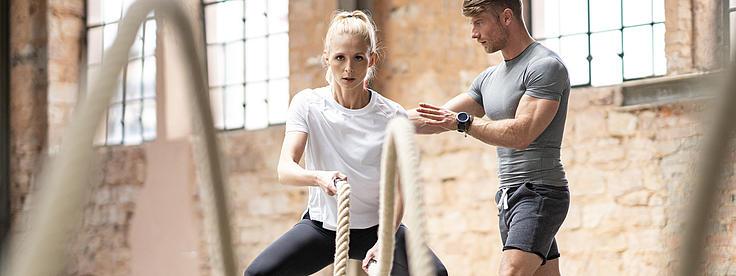 Eine Frau beim Training unterstützt von einem Trainer