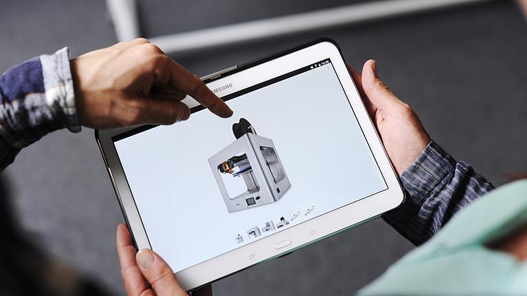 Zwei Männerhände halten ein Tablet. Eine weitere Männerhand zeigt auf die Darstellung einer technischen Anlage auf dem Tablet.
