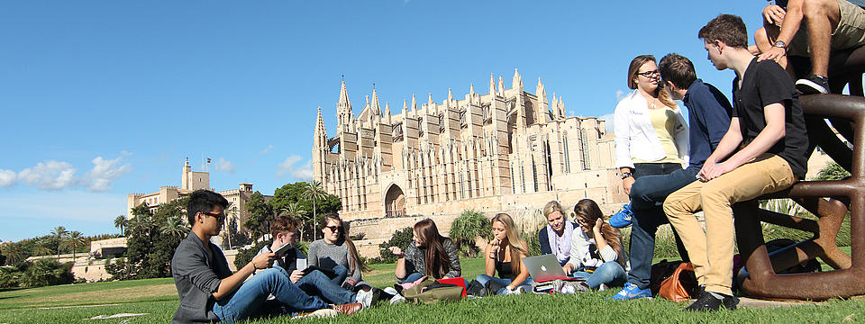 Studierende sitzend vor der Kathedrale von Palma
