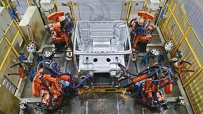 Schweißroboter arbeiten an einem Karosserieteil in einer Produktionshalle