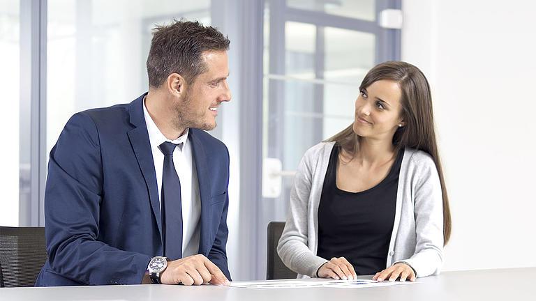 Zwei Menschen sitzen an einem Tisch und unterhalten sich.