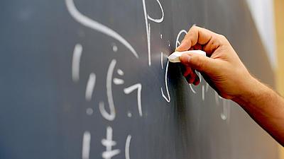 Eine Hand schreibt mit Kreide matheamtische Formeln auf eine Tafel.