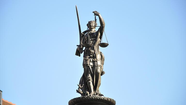 Aufgenommen aus der Froschperspektive sieht man eine Statue der Göttin der Gerechtigkeit, Justitia vor blauem Himmel.