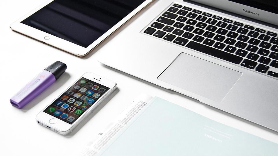 Auf einem Schreibtisch liegen Handy, Tablet, Laptop und Notizen.
