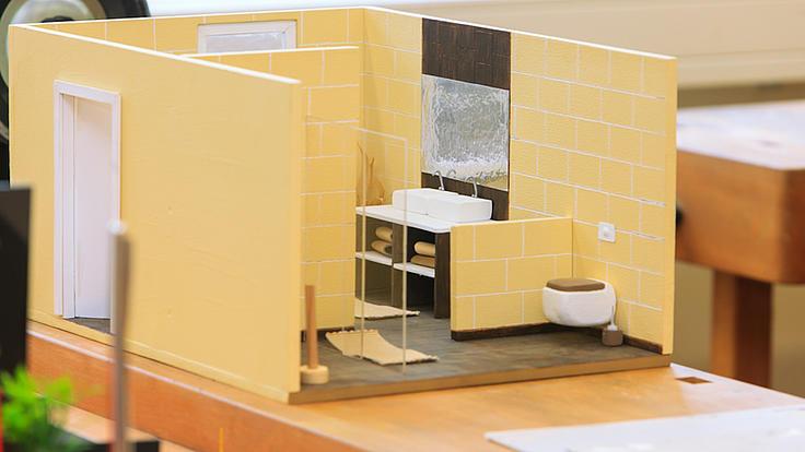 Ein Mini-Modell eines Raums mit Mini-Möbeln zur beispielhaften Gestaltung einer Inneneinrichtung.