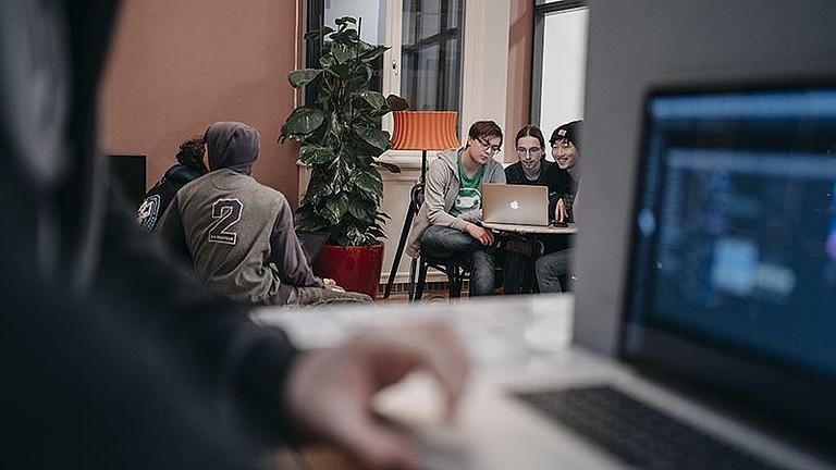 Im Vordergrund arbeitet ein Student am Laptop. Im HIntergrund sitzen drei Studenten vor einem Laptop.