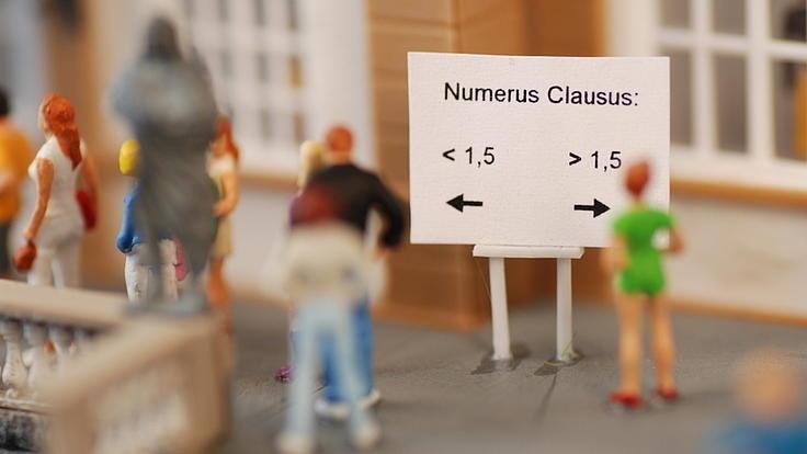 Mehrere Miniatur-Figuren stehen  vor einem Schild. Auf dem Schild sind die Worte