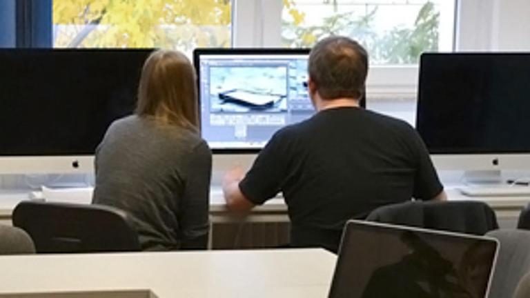 Zwei Studierende sitzen an einem PC.
