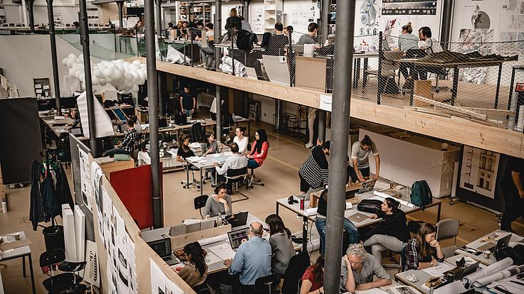 Studenten in einem zweistöckigen Ateilier mit Plänen und PC's
