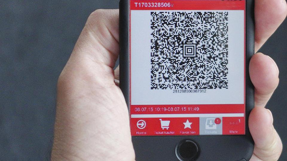 Eine Hand hält ein Handy mit einer App auf der ein Online-Fahrschein mit QR-Code zu sehen ist.