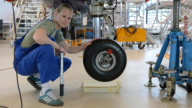 Eine junge Frau beim Radwechsel am Flugzeug.