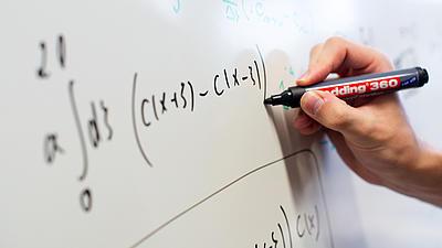 Eine Hand schreibt eine mathematische Formel auf eine Tafel.