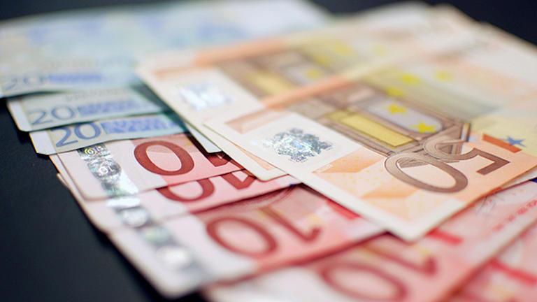 Auf einer dunklen Fläche liegen aufgefächert Geldscheine. Es handelt sich um 20 Euro-Scheine und 10 Euro-Scheine, darauf liegen 50 Euro-Scheine.