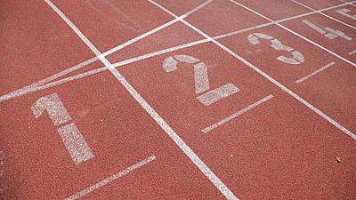 Nahaufnahme der Startplätze eins bis vier auf einer roten Laufbahn. Die Markierungslinien und die Zahlen sind weiß.