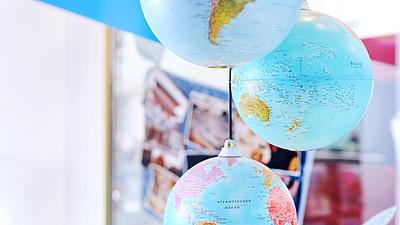 Mehrere Globen hängen von der Decke.