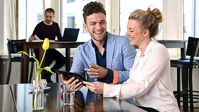 Zwei junge Menschen schauen in ein Tablet.