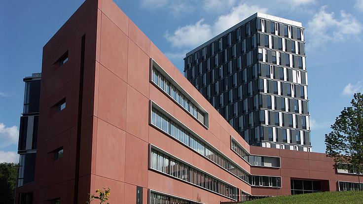 Universtiätsgebäude mit braunroter Fassade, blauem Himmel und Federwolken