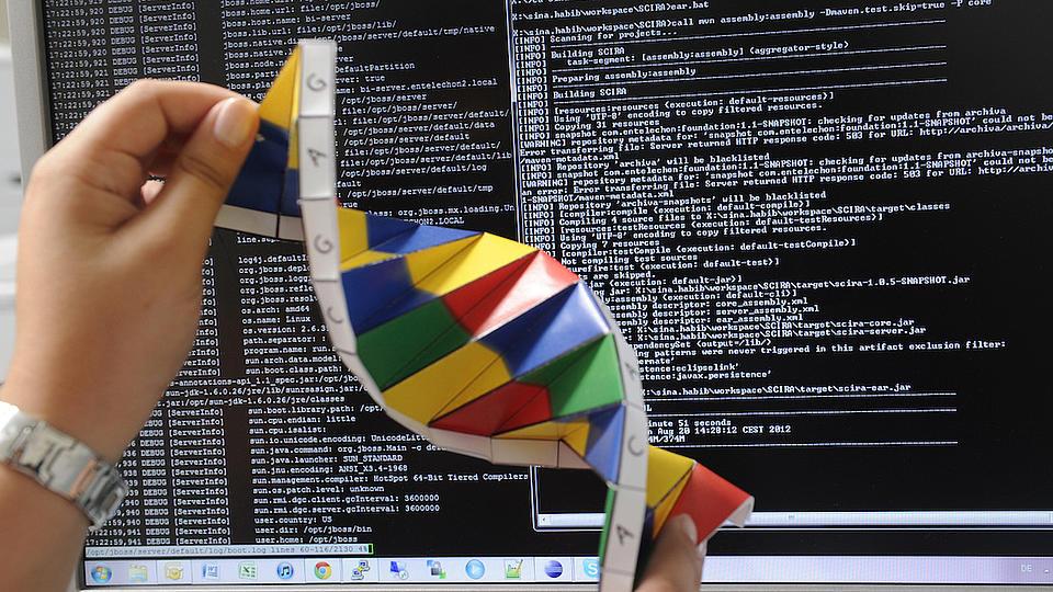 Ein symoblischer DNA-Strang wird vor einem Monitor in den Händen gehalten.