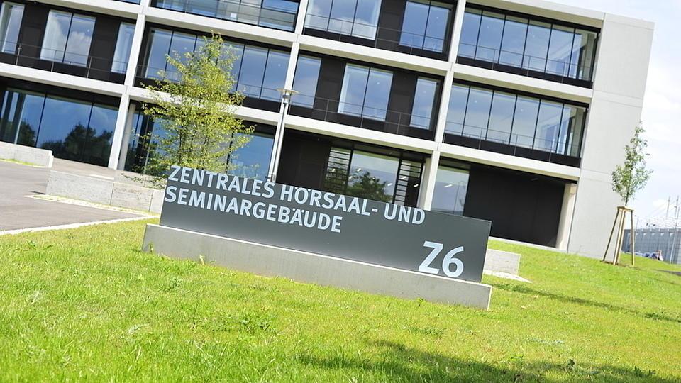 Außenaufnahme eines modernen dreistöckigen Gebäudes auf einer grünen Wiese. Vor dem Gebäude steht ein Schild mit der Aufschrift: Zentrales Hörsaal- und Seminargebäude.