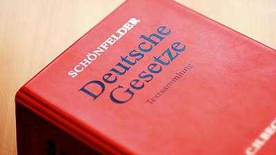 Teilaufnahme eines roten Plastikordners einer Loseblattsammlung mit der Aufschrift Deutsche Gesetze - Textsammlung.
