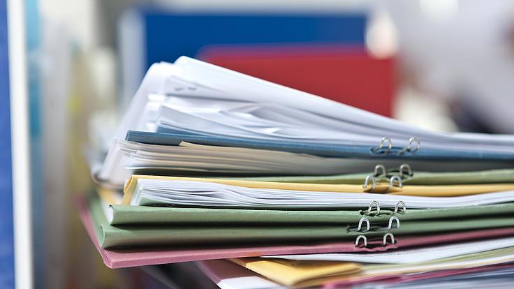 Auf einem Tisch liegt ein Stapel mit Akten und verschiedenen Dokumenten.