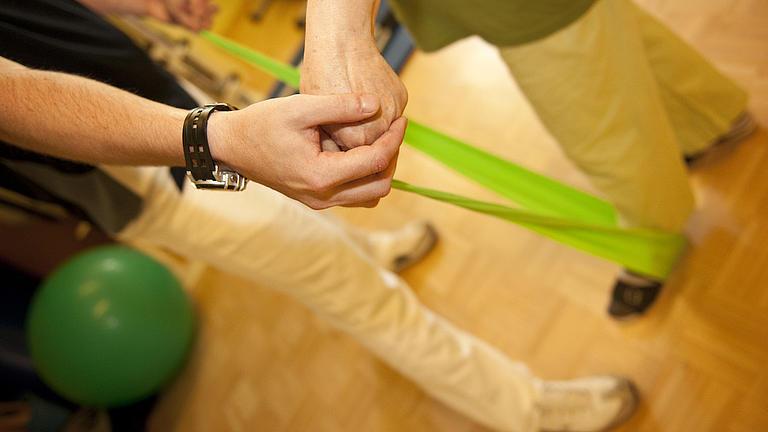 Auf hellem Holzboden sieht man zwei männlich Personen brustabwärts. Die eine Person wird von der anderen bei einer Übung mit einem leuchtend grünen Fitnessband angeleitet