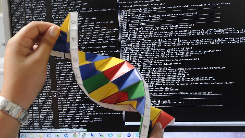 Eine Bioinformatikerin zeigt ein Modell eines DNA-Strangs.