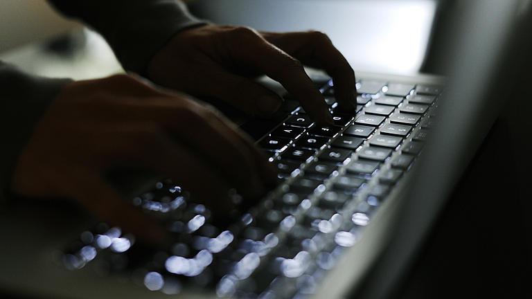 Zwei Hände tippen auf einer Laptop-Tastatur.