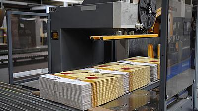 Auf einem Förderband unter einer dunklen Maschine für die Herstellung von Kartonagen liegen drei Stapel mit fertigen Kartons. Die Stapel werden von Kunststoffbändern zusammengehalten.