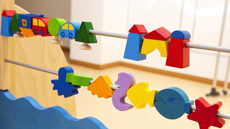 An zwei übereinander hängenden Metallstangen sind verschiedene bunte Holzspielzeuge aufgefädelt.