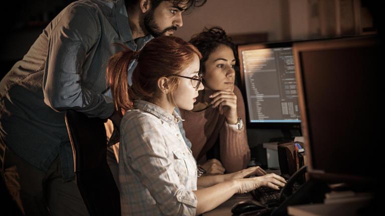Eine Gruppe sitzend am Tisch vor Rechnern.
