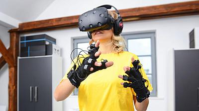 Eine junge Frau mit einer VR-Brille auf dem Kopf.