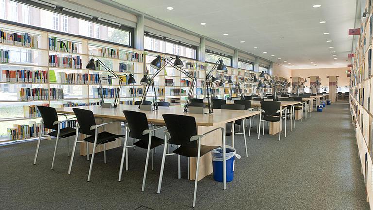 Blick in einen Lesesaal mit mehreren Tischreihen, an denen schwarze Stühle stehen.