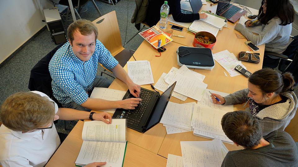 Mehrere Studierende sitzen an einem Tisch und lernen.