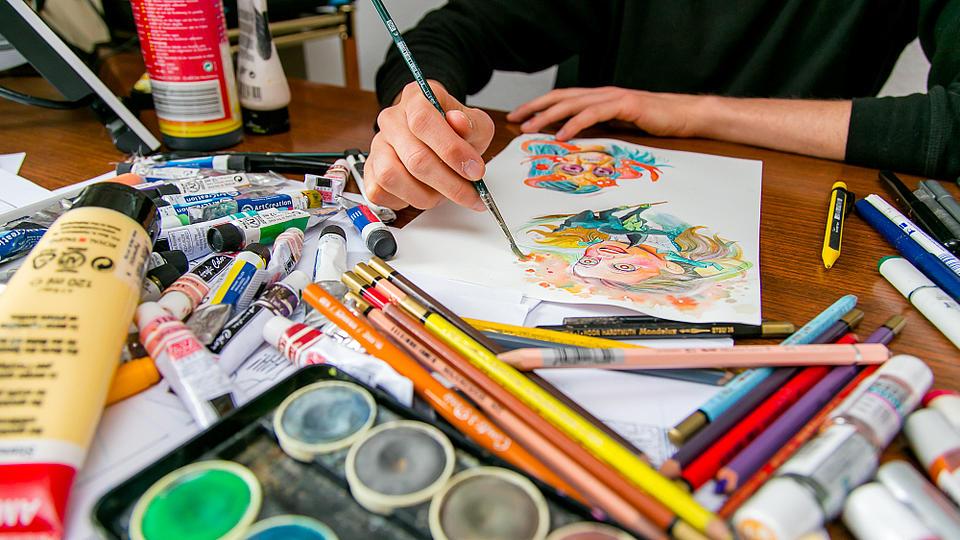 Ein Comiczeichner malt mit Wasserfarben an einer Figur.