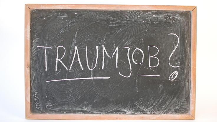 Auf einer Schreibtafel mit Holzrand steht in Großbuchstaben das Wort