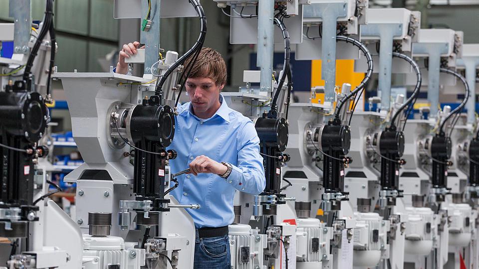 Ein junger Mann steht in einer Produktionshalle und kontrolliert ein Bauteil.