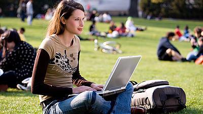 Studentin sitzend im grünen Gras mit Laptop auf dem Schoß