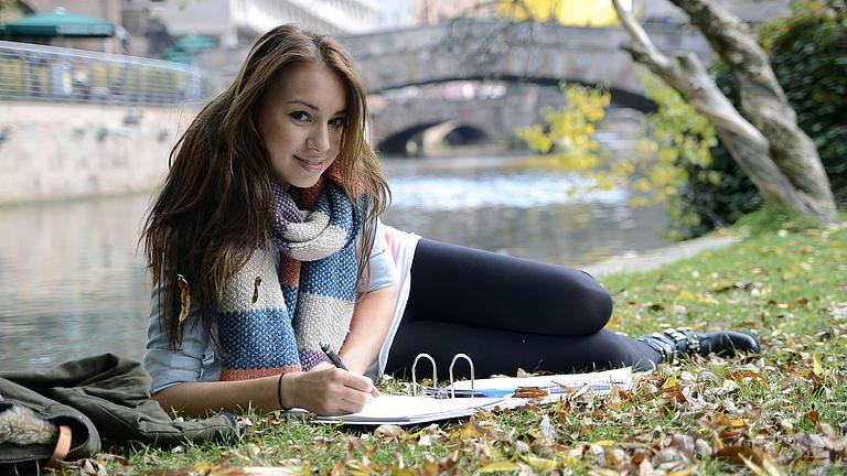 Eine Studentin liegt auf einer Wiese und lernt.