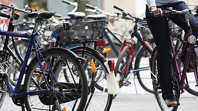 Verschiedene abgestellte Fahrräder auf einem Platz, auf der rechten Bildseite erkennt man die Beine einer vorbeifahrenden Radfahrerin.