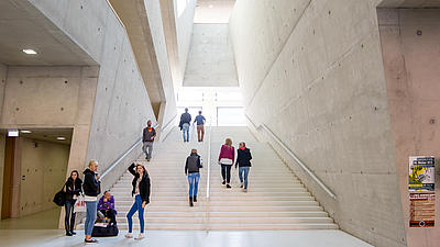 Studierende stehen im Foyer einer Hochschule.